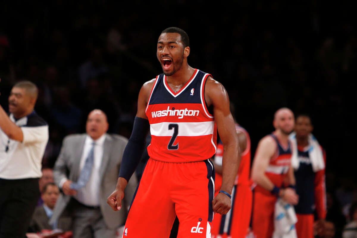 Washington Wizards' John Wall (2) celebrates after scoring a basket and drawing a foul against the New York Knicks during the first half of an NBA basketball game Monday, Dec. 16, 2013, in New York. (AP Photo/Jason DeCrow)
