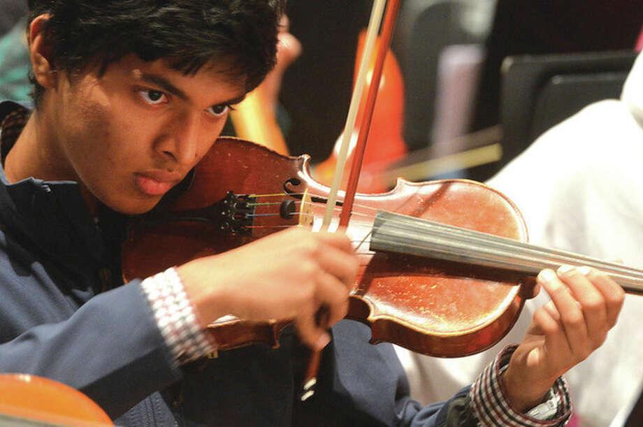 Hour Photo/Alex von Kleydorff. Aman Karhnakaran on violin, follows Ron Secchi during rehearsal for the Poinsettia concert this week at Brien McMahon High School