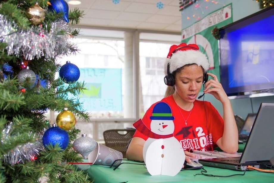 "In this Dec. 12, 2013 photo provided by the University of Illinois, student and Snyder Hall resident at the University of Illinois, Katherine Moss sings to callers as part of the hall's annual Dial-A-Carol program in Champaign, Ill. The student-run project is a hotline of sorts for people who prefer their holiday carols sung live by amateurs. The program was started in 1960 by a former hall secretary, Betty Gordon, and a group of the dorm's residents. Last year, the student volunteers took more than 4,000 calls from people all over the world requesting ""Jingle Bells,"" ""White Christmas"" and ""Rudolph the Red-Nosed Reindeer."" (AP Photo/University of Illinois, Claire Everett) / University of Illinois"