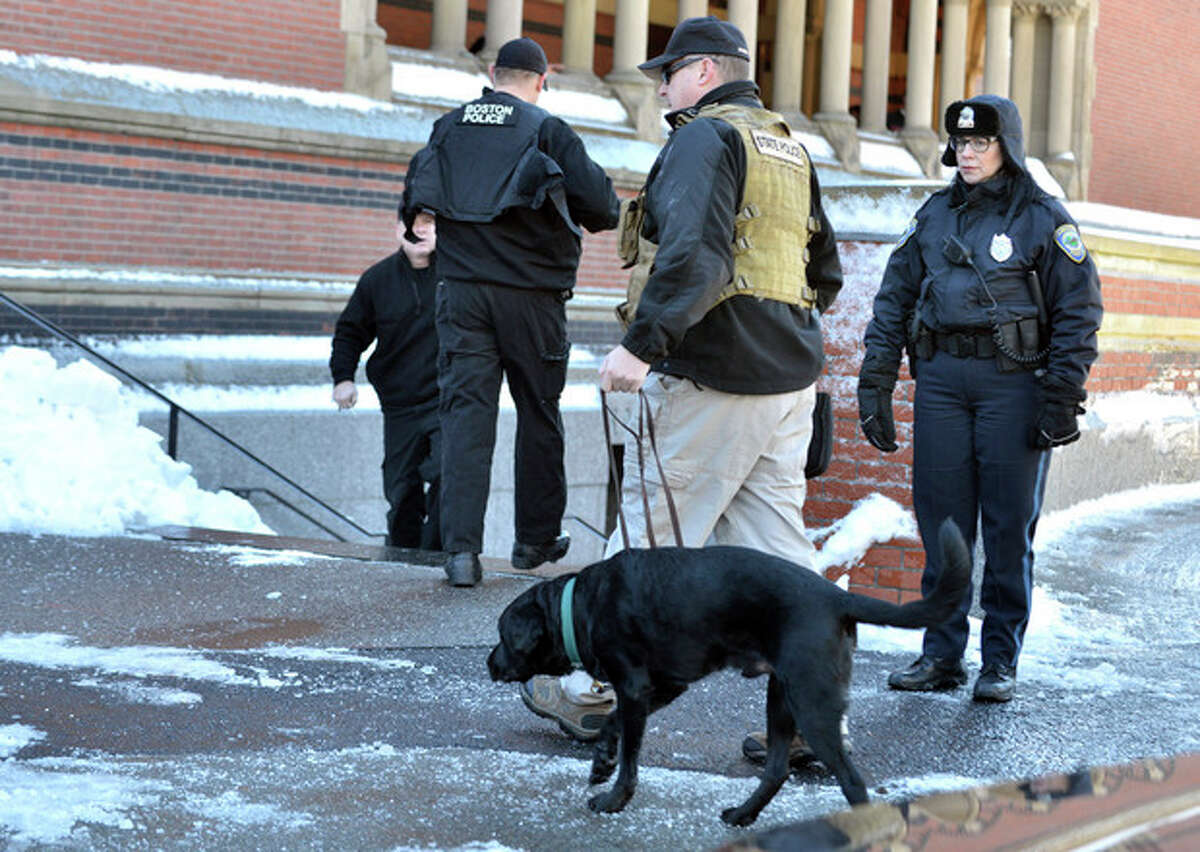 A police officer leads a dog into a building at Harvard University in Cambridge, Mass., Monday, Dec. 16, 2013. Four buildings on campus were evacuated Monday after campus police received an unconfirmed report that explosives may have been placed inside, interrupting final exams. (AP Photo/Josh Reynolds)
