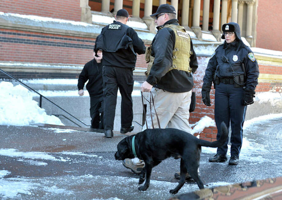 A police officer leads a dog into a building at Harvard University in Cambridge, Mass., Monday, Dec. 16, 2013. Four buildings on campus were evacuated Monday after campus police received an unconfirmed report that explosives may have been placed inside, interrupting final exams. (AP Photo/Josh Reynolds) / AP