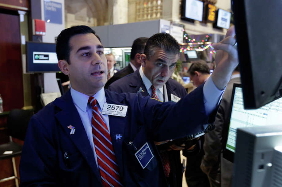 In this Monday, Dec. 16, 2013 photo, specialist William Geier, left, works on the floor of the New York Stock Exchange. Investors took to the sidelines Tuesday, Dec. 17, 2013, a day ahead of a key policy decision from the U.S. Federal Reserve that may see the central bank reduce its massive monetary stimulus. (AP Photo/Richard Drew) / AP