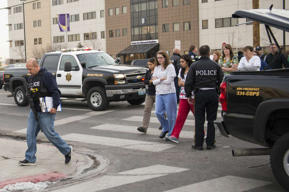 Officers escort witnesses to a waiting bus at the Renown Regional Medical Center after a lone gunman shot and injured four people before killing himself , Tuesday, Dec. 17, 2013 in Reno, Nev. (AP Photo/Scott Sady)