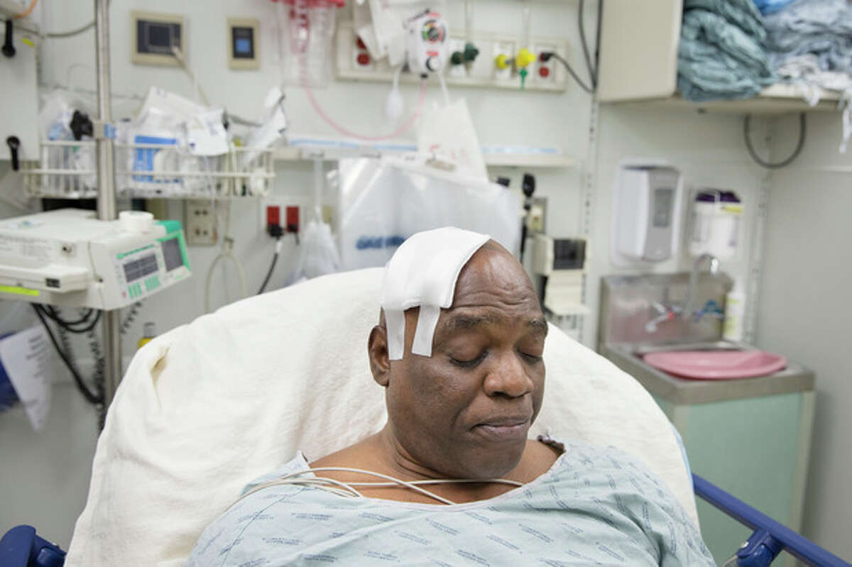 Cecil Williams rests in his hospital bed following a fall onto subway tracks from the platform at 145th Street, Tuesday, Dec. 17, 2013, in New York. Williams, 61 and blind, says he fainted while holding onto his black labrador guide dog, Orlando, who tried to save him from falling. (AP Photo/John Minchillo)