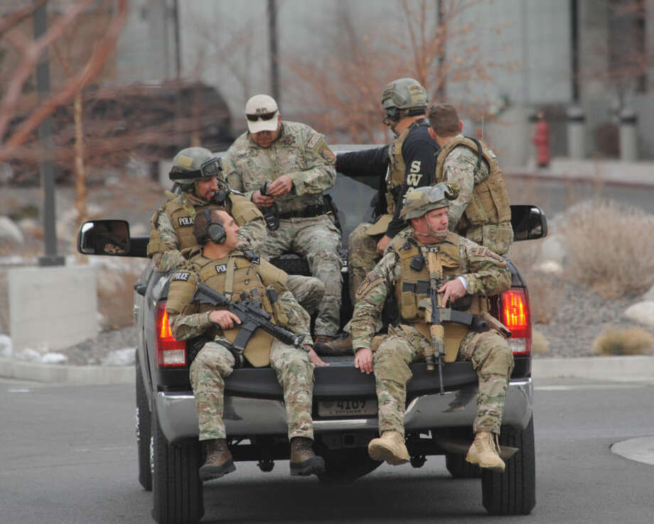 SWAT team members are trucked from near the Renown helicopter pad to the Renown Medical Center where a lone gunman shot and injured four people before killing himself at a sprawling medical campus Tuesday, Dec. 17, 2013 in Reno, Nev. (AP Photo/The Reno Gazette-Journal, Tim Dunn) NO SALES; NEVADA APPEAL OUT; SOUTH RENO WEEKLY OUT