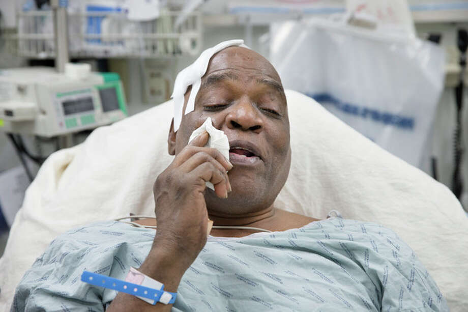 Cecil Williams wipes tears from his face during an interview as he rests in his hospital bed following a fall onto subway tracks from the platform at 145th Street, Tuesday, Dec. 17, 2013, in New York. Williams, 61 and blind says he fainted while holding onto his black Labrador guide dog, Orlando, who tried to save him from falling. (AP Photo/John Minchillo) / FR170537 AP