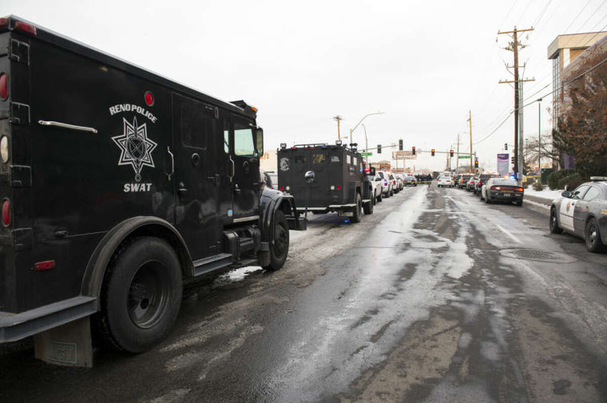 Police vehicles gather in front of the Renown Regional Medical Center after a lone gunman shot and injured four people before killing himself , Tuesday, Dec. 17, 2013 in Reno, Nev. (AP Photo/Scott Sady)