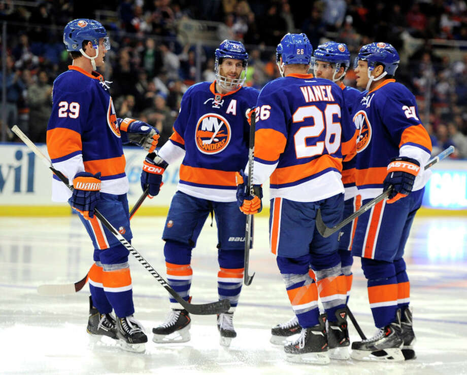New York Islanders', from left, Brock Nelson (29), Andrew MacDonald, Thomas Vanek (26), John Tavares and Kyle Okposo (21) celebrate Okposo's goal against the Tampa Bay Lightning in the second period of an NHL hockey game on Tuesday, Dec. 17, 2013, in Uniondale, N.Y. (AP Photo/Kathy Kmonicek) / FR170189 AP