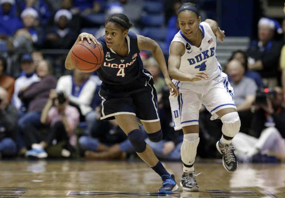 Duke's Chloe Wells chases Connecticut's Moriah Jefferson (4) during the second half of an NCAA college basketball game in Durham, N.C., Tuesday, Dec. 17, 2013. Connecticut won 83-61. (AP Photo/Gerry Broome)
