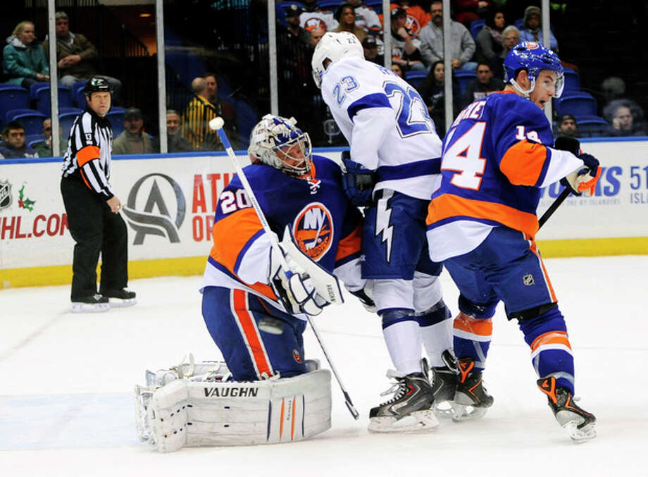 The puck flies by New York Islanders goalie Evgeni Nabokov (20) as he collides with Tampa Bay Lightning J.T. Brown (23) as New York Islanders' Thomas Hickey (14) defends in the first period of an NHL hockey game on Tuesday, Dec. 17, 2013, in Uniondale, N.Y. (AP Photo/Kathy Kmonicek) / FR170189 AP