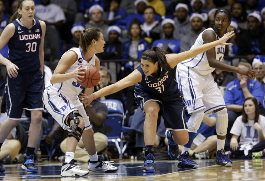 Connecticut's Stefanie Dolson (31) reaches for the ball against Duke's Haley Peters, left, and Elizabeth Williams, right, during the second half of an NCAA college basketball game in Durham, N.C., Tuesday, Dec. 17, 2013. Connecticut won 83-61.(AP Photo/Gerry Broome)