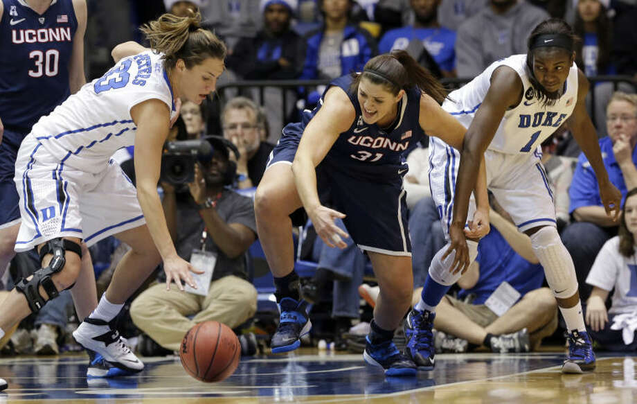 Connecticut's Stefanie Dolson (31) struggles for possession of the ball with Duke's Haley Peters, left, and Elizabeth Williams (1) during the second half of an NCAA college basketball game in Durham, N.C., Tuesday, Dec. 17, 2013. Connecticut won 83-61.(AP Photo/Gerry Broome)