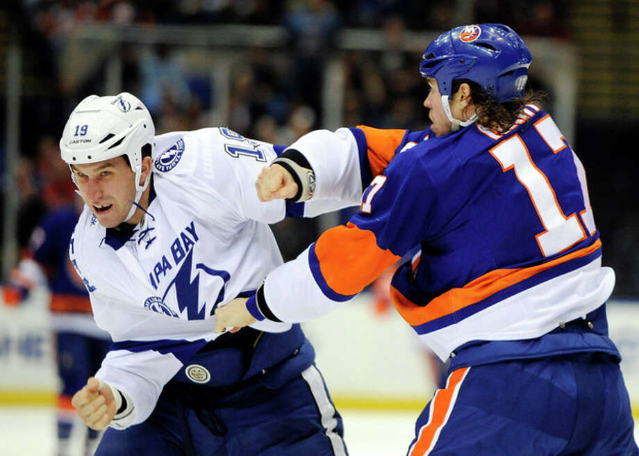 Tampa Bay Lightning' B.J. Crombeen (19) and New York Islanders' Matt Martin (17) exchange punches on the ice in the second period of an NHL hockey game on Tuesday, Dec. 17, 2013, in Uniondale, N.Y. (AP Photo/Kathy Kmonicek) / FR170189 AP