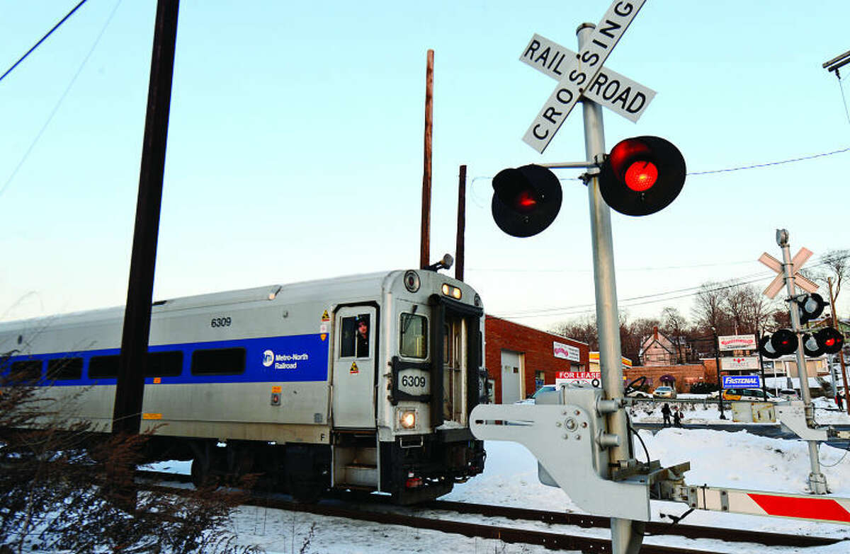 Hour photo / Erik Trautmann A Norwalk public school bus broke down on the railroad crossing at Broad St. as an oncoming commuter train stopped in time to avoid a crash.
