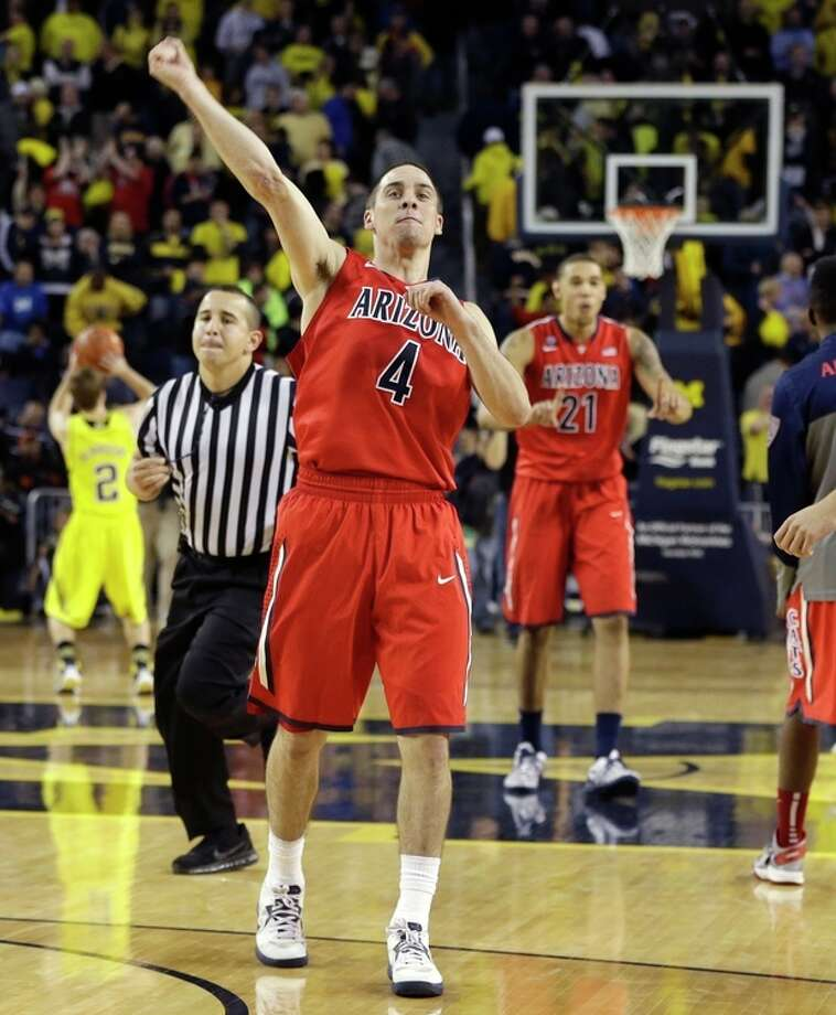 Arizona guard T.J. McConnell (4) celebrates after the Wildcats defeated Michigan 72-70 in an NCAA college basketball game in Ann Arbor, Mich., Saturday, Dec. 14, 2013. (AP Photo/Carlos Osorio) / AP