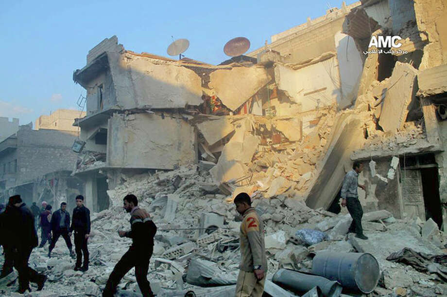 In this Sunday, Dec. 15, 2013 citizen journalism image provided by Aleppo Media Center, AMC, which has been authenticated based on its contents and other AP reporting, Syrians inspect the rubble of damaged buildings following a Syrian government airstrike in Aleppo, Syria. The Britain based Syrian Observatory for Human Rights said Monday that dozens of children were among scores killed in airstrikes on several opposition areas a day earlier. (AP Photo/Aleppo Media Center AMC) / Aleppo Media Center AMC