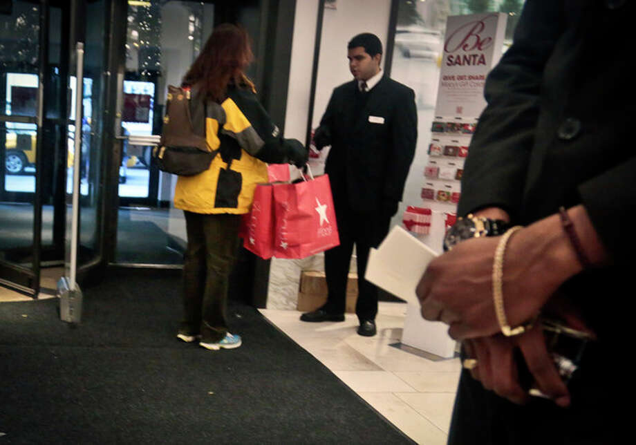 In this Dec. 13, 2013 photo, a security agent checks the bags of a shopper at Macy's in New York. Claims over racial profiling at department stores in New York have helped expose the practice in more than 40 states of retailers holding shoplifting suspects and assessing fines, even if a person hasn't yet technically stolen anything. At Macy's flagship store, suspects are held in cells, asked to sign an admission of guilt and pay hundreds in fines. (AP Photo/Bebeto Matthews) / AP