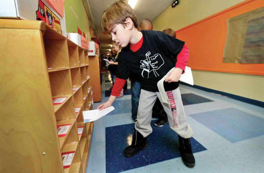 Hour photo / Erik Trautmann Columbus Magnet School 2nd grader Noah Wasserman particpates in the school's annual Columbus Mail Service program where students learn how the postal system works. / (C)2013, The Hour Newspapers, all rights reserved