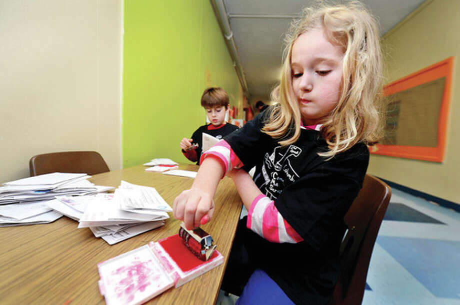 Above, Columbus Magnet School 2nd grader Mary Kate Hopkins and Noah Wasserman sort and cancel mail as they learn how the postal system works. Below, 2nd-grader Noah Wasserman participates in the school's Columbus Mail Service. / (C)2013, The Hour Newspapers, all rights reserved