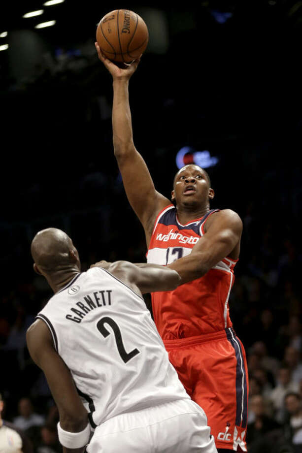 Washington Wizards' Kevin Seraphin shoots over Brooklyn Nets' Kevin Garnett during the first half of an NBA basketball game Wednesday, Dec. 18, 2013, in New York. (AP Photo/Seth Wenig)