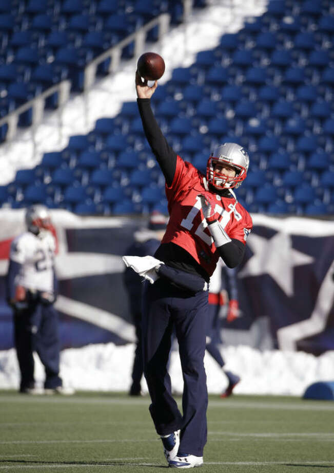 New England Patriots quarterback Tom Brady (12) throws a pass during a stretching and drills session before practice begins at the NFL football team's facility in Foxborough, Mass., Wednesday, Dec. 18, 2013. The Patriots play the Baltimore Ravens Sunday in Maryland. (AP Photo/Stephan Savoia)