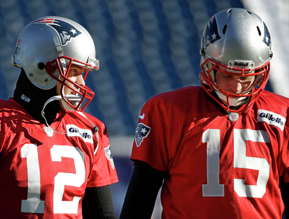 New England Patriots quarterbacks Tom Brady (12) and Ryan Mallett talk as they walk across the field during a stretching and drills session before practice begins at the NFL football team's facility in Foxborough, Mass., Wednesday, Dec. 18, 2013. The Patriots play the Baltimore Ravens Sunday in Maryland. (AP Photo/Stephan Savoia) / AP