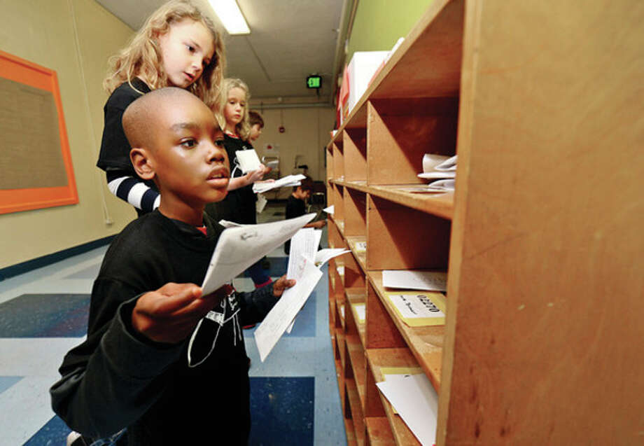 Hour photos / Erik TrautmannColumbus Magnet School 2nd-graders Jelani Hampton and Seve Zurkowski particpate in the school's annual Columbus Mail Service program by sorting mail as they learn how the postal system works. / (C)2013, The Hour Newspapers, all rights reserved