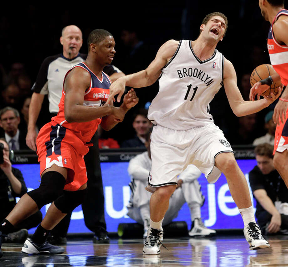 Washington Wizards' Kevin Seraphin, left, fouls Brooklyn Nets' Brook Lopez during the first half of the NBA basketball game Wednesday, Dec. 18, 2013, in New York. (AP Photo/Seth Wenig) / AP