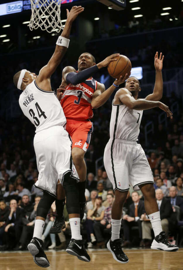 Washington Wizards' Bradley Beal, center, drives to the basket through Brooklyn Nets' Paul Pierce, left, and Joe Johnson during the first half of an NBA basketball game Wednesday, Dec. 18, 2013 in New York. (AP Photo/Seth Wenig)