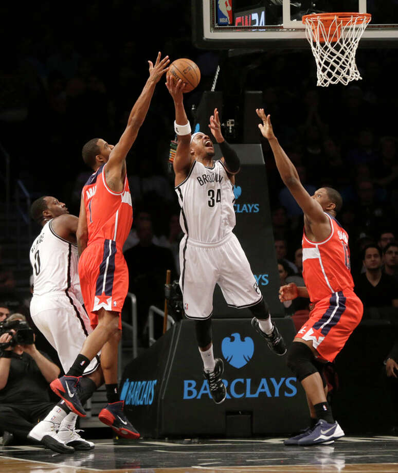 Brooklyn Nets' Paul Pierce puts up a shot between Washington Wizards' Kevin Seraphin, right, and Trevor Ariza during the first half of an NBA basketball game Wednesday, Dec. 18, 2013, in New York. (AP Photo/Seth Wenig) / AP