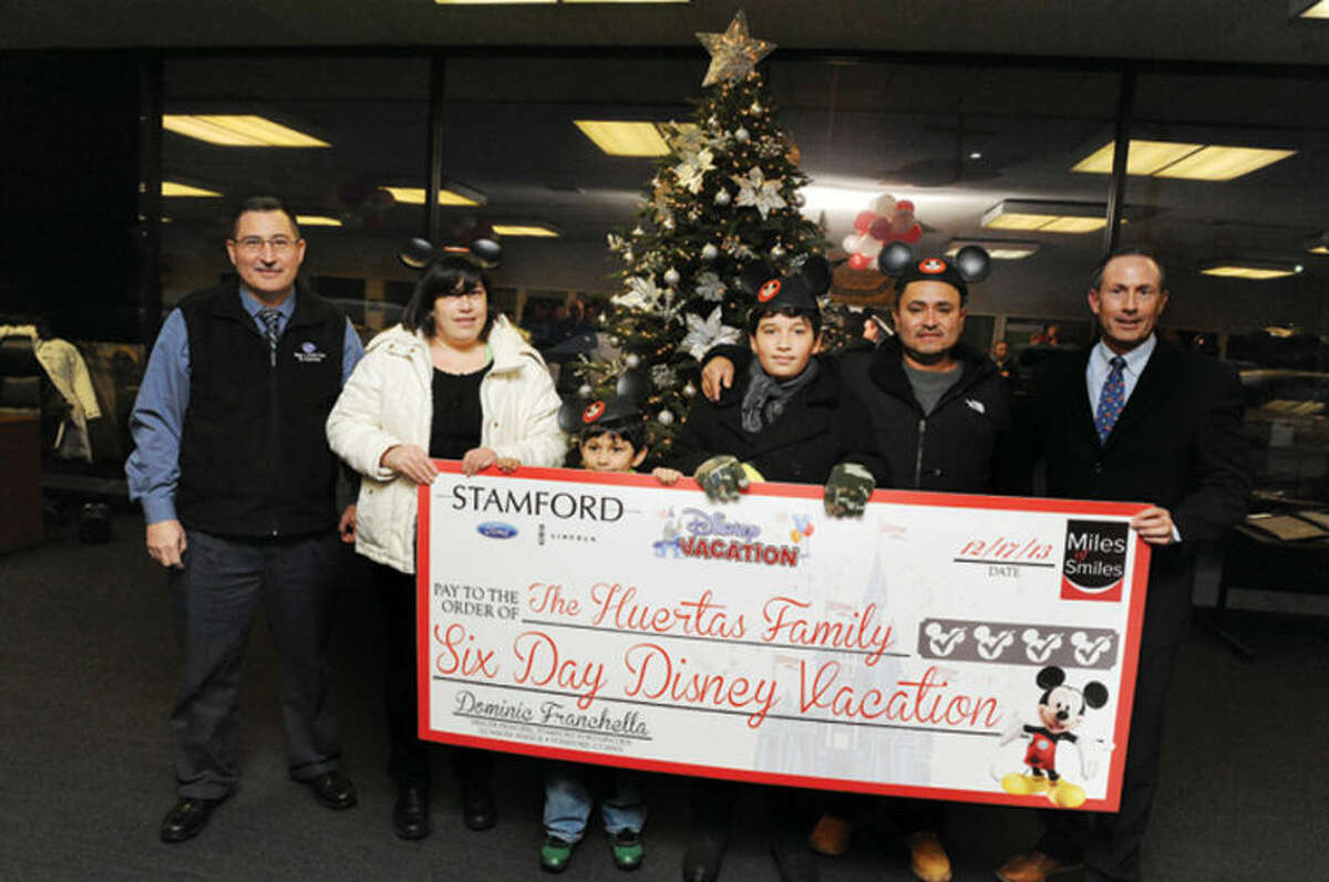 Stamford Ford Lincoln gave away a trip to Disney World Tuesday to the Huertas family. From left, Dr. Michael Cotela of the Boys & Girls Club in Stamford; Marene Huertasand; her sons, George and Anthony; her husband George; and Dominic Franchella, dealer principal at Stamford Ford Lincoln.