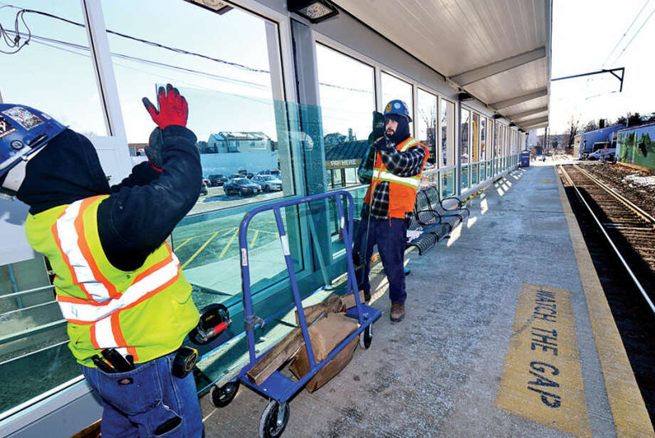 John Gallo and Kurt Hatrick of Cherry Hill Glass in Branford put new glass panels at the Glenbrook train station Thursday as part of the improvements there. Stamford holds a public planning meeting regarding the improvements to Glenbrook and Springdale train stations.