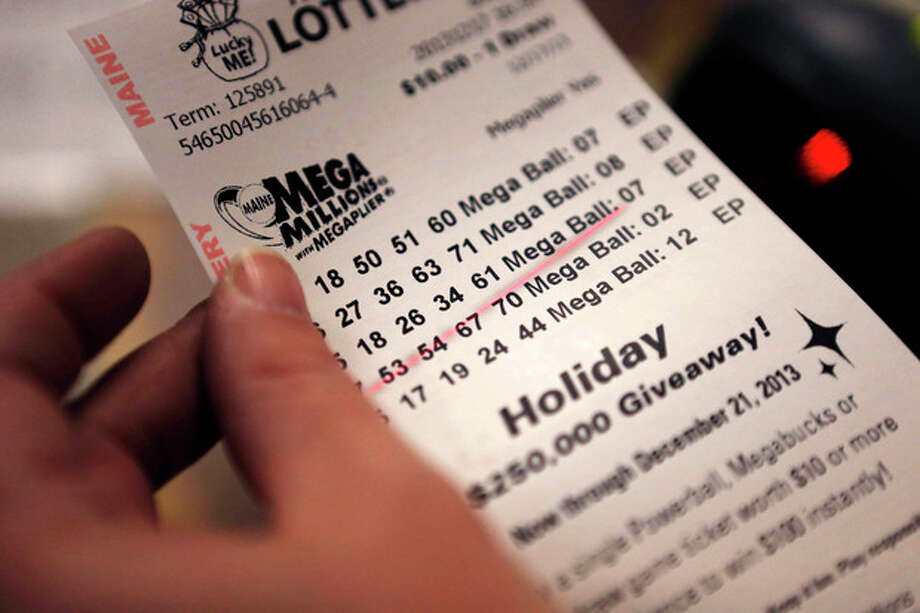 A cashier holds a Mega Millions lottery ticket at a convenience store in Lisbon, Maine, Tuesday, Dec. 17, 2013. With tickets selling well, the jackpot for tonight's drawing is now at an estimated $636 million, the second-biggest lottery prize in U.S. history. (AP Photo/Robert F. Bukaty) / AP