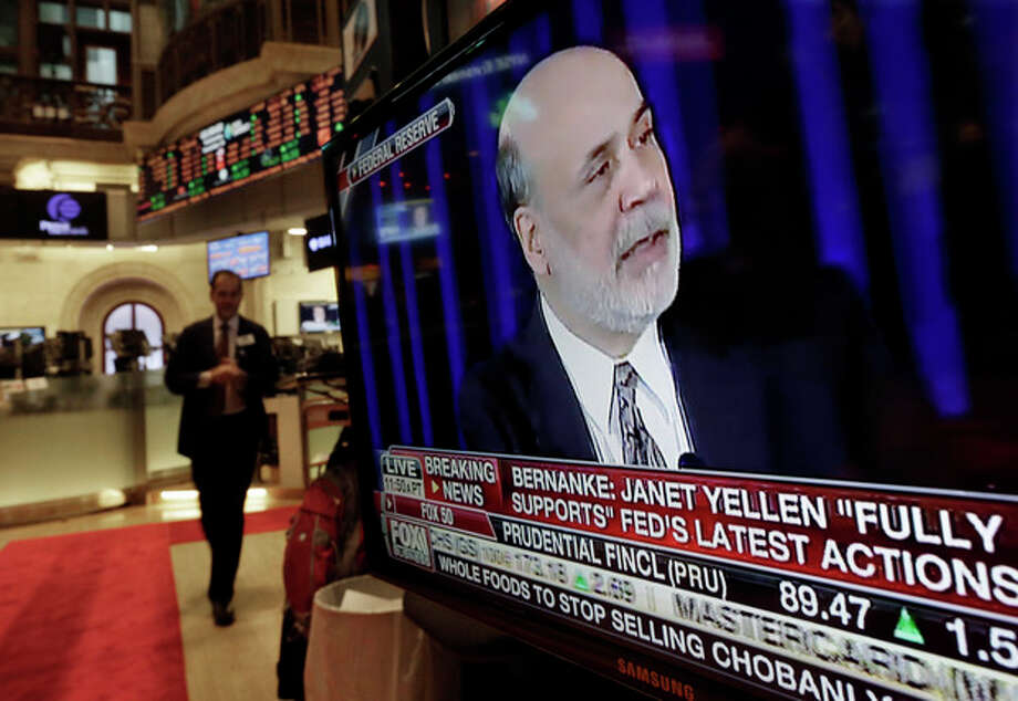 The news conference of Federal Reserve Chairman Ben Bernanke appears on a television screen at a trading post on the floor of the New York Stock Exchange, Wednesday, Dec. 18, 2013. The Federal Reserve has decided to reduce its stimulus for the U.S. economy because the job market has shown steady improvement. The Fed will trim its $85 billion a month in bond purchases by $10 billion starting in January. (AP Photo/Richard Drew) / AP