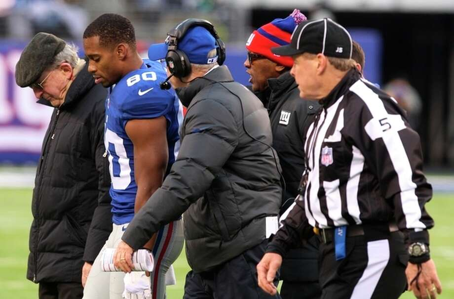 New York Giants wide receiver Victor Cruz (80) walks off the field with head coach Tom Coughlin, center left, during the second half of an NFL football game against the Seattle Seahawks, Sunday, Dec. 15, 2013, in East Rutherford, N.J. (AP Photo/Peter Morgan) / AP