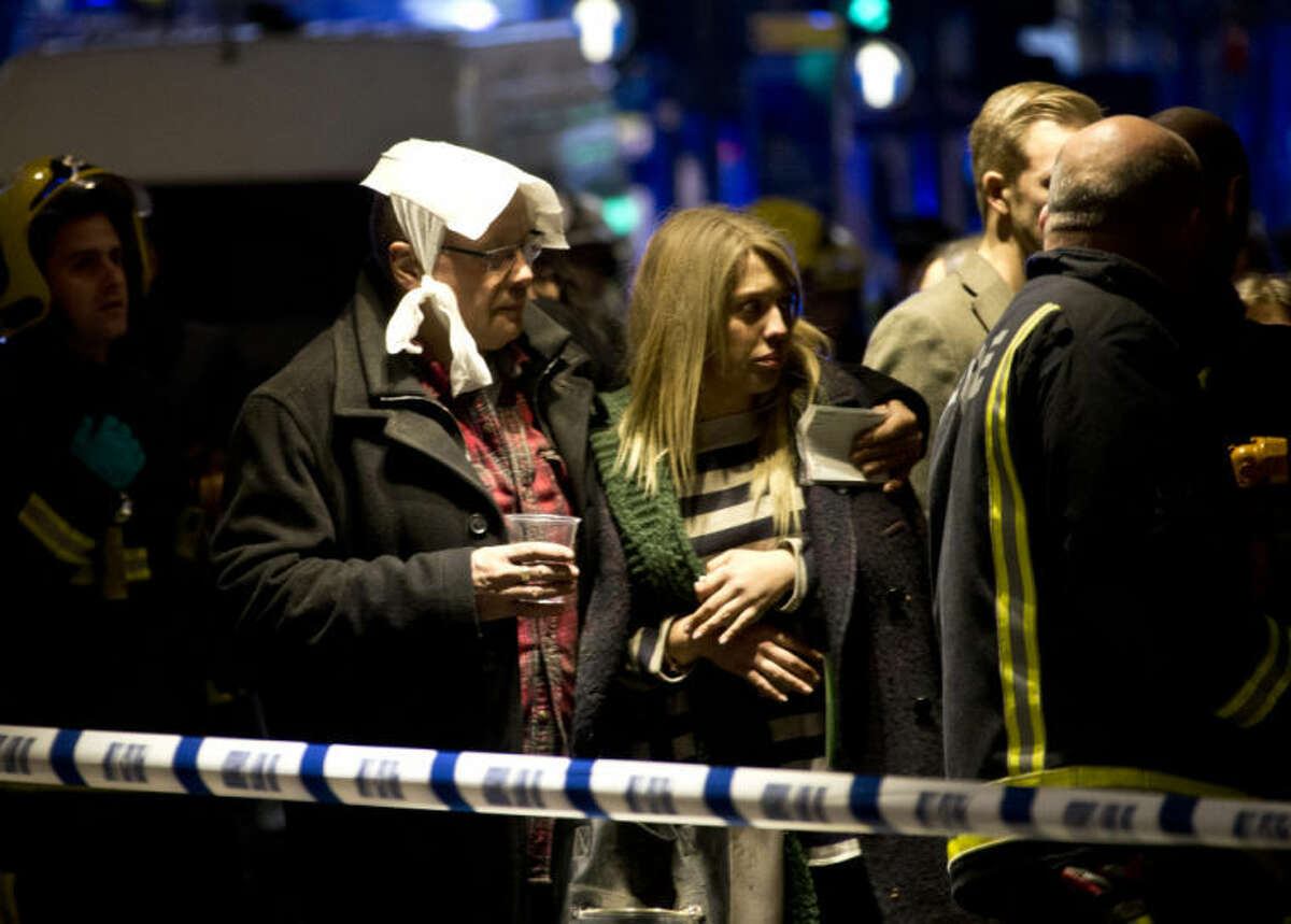 """A bandaged man comforts a woman following an incident at the Apollo Theatre, in London's Shaftesbury Avenue, Thursday evening, Dec. 19, 2013, during a performance , with police saying there were """"a number"""" of casualties. It wasn't immediately clear if the roof, ceiling or balcony had collapsed. The London Fire Brigade said the theatre was almost full, with around 700 people watching the performance. A spokesman added: """"It's thought between 20 and 40 people were injured."""" (AP Photo by Joel Ryan, Invision)"""