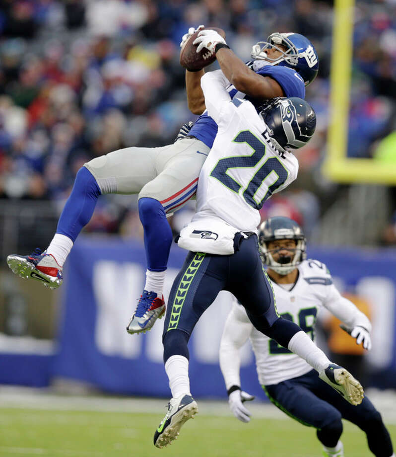 New York Giants wide receiver Victor Cruz, left, makes a catch as Seattle Seahawks cornerback Jeremy Lane defends on the play during the second half of an NFL football game, Sunday, Dec. 15, 2013, in East Rutherford, N.J. Cruz was banged up on the play and left the game with an injury. (AP Photo/Kathy Willens) / AP