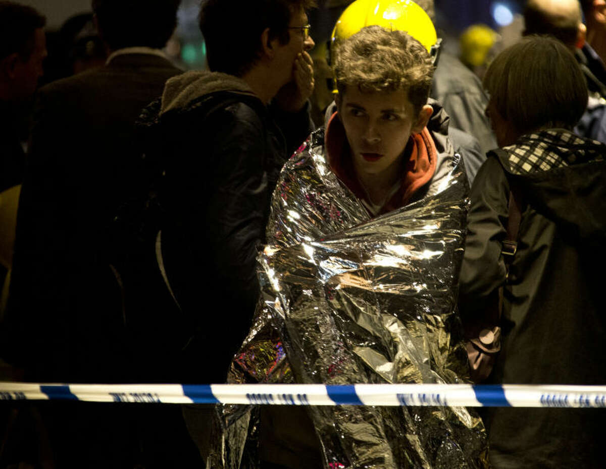 """A man wraps himself in an emergency foil blanket provided by rescue services following an incident at the Apollo Theatre, in London's Shaftesbury Avenue, Thursday evening, Dec. 19, 2013 during a performance , with police saying there were """"a number"""" of casualties. It wasn't immediately clear if the roof, ceiling or balcony had collapsed. The London Fire Brigade said the theatre was almost full, with around 700 people watching the performance. A spokesman added: """"It's thought between 20 and 40 people were injured."""" (AP Photo by Joel Ryan, Invision)"""