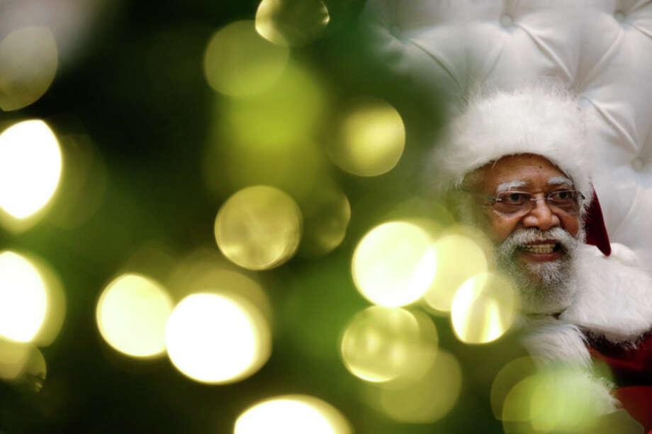 Dressed as Santa Claus, Langston Patterson, 77, poses for photos at Baldwin Hills Crenshaw Plaza mall in Los Angeles on Monday, Dec. 16, 2013. (AP Photo/Jae C. Hong) / AP