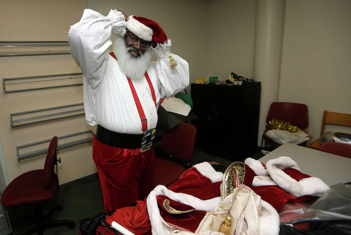 In this Tuesday, Dec. 17, 2013 photo, Dee Sinclair, who bills himself as the real black Santa prepares to visit children at a library, in Atlanta. Fusing the icon of the long-white beard and red suit from American artist Norman Rockwell and later Coca-Cola, in recent years the new Santas incorporate their own ethnic take on the Christmastime figure with various interpretations. (AP Photo/John Bazemore)