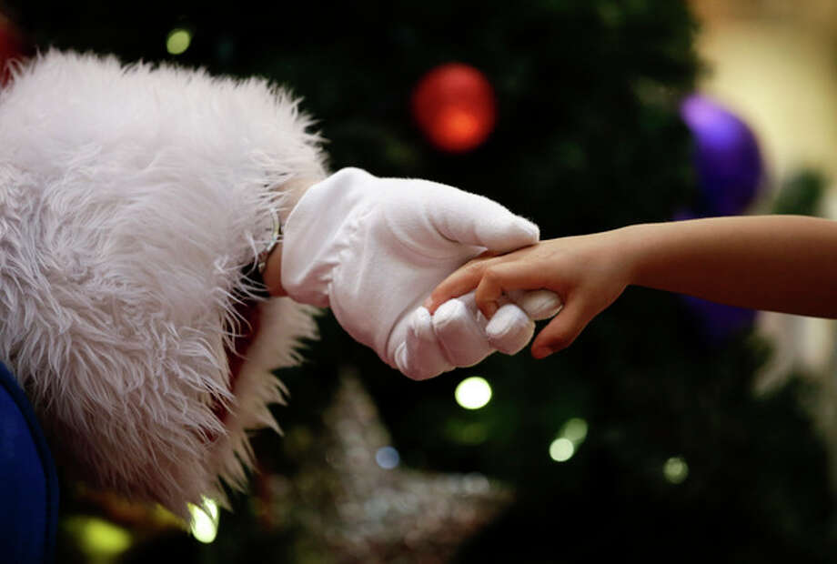 Dressed as Santa Claus, Mark Tate, left, holds the hand of Emmitt Lopez at a mall on Tuesday, Dec. 17, 2013, in Cerritos, Calif. (AP Photo/Jae C. Hong) / AP
