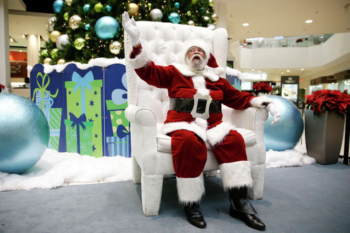 Dressed as Santa Claus, Langston Patterson, 77, waves at shoppers at Baldwin Hills Crenshaw Plaza in Los Angeles on Monday, Dec. 16, 2013. Andrew Chesnut, the Bishop Walter F. Sullivan Chair in Catholic Studies at Virginia Commonwealth University, said depictions of Santa Claus as a white man came about mainly because he was a European import, a blend of the Dutch Sinterklaas and British folklore character Father Christmas, with elements of Saint Nicholas, a 4th-century Greek bishop in modern-day Turkey. (AP Photo/Jae C. Hong)