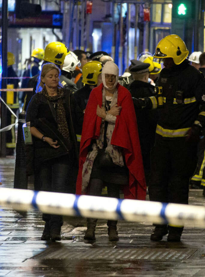 "A woman walks, bandaged and wearing a blanket given by emergency services, following an incident at the Apollo Theatre, in London's Shaftesbury Avenue, Thursday evening, Dec. 19, 2013, during a performance at the height of the Christmas season, with police saying there were ""a number"" of casualties. It wasn't immediately clear if the roof, ceiling or balcony had collapsed during a performance. Police said they ""are aware of a number of casualties,"" but had no further details. (AP Photo by Joel Ryan, Invision)"
