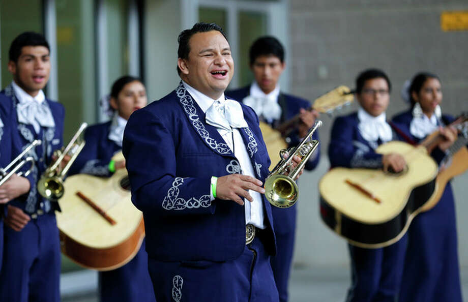 "In this Sept. 29, 2013 photo, Ramon Rivera leads his students in Wenatchee High School's ""Mariachi Huenachi"" program during a performance outside CenturyLink Field prior to a Seattle Sounders MLS soccer game in Seattle. Officials say the program, created to connect children of farmworkers in the heart of Washington state with their heritage, has helped students center themselves and has even raised graduation rates. (AP Photo/Ted S. Warren) / AP"