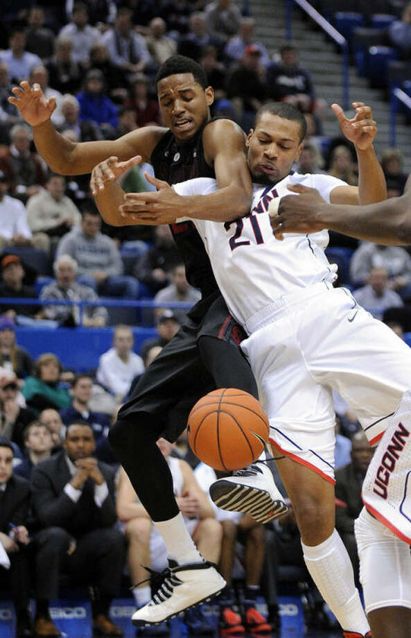 Stanford's Anthony Brown, left, and Connecticut's Omar Calhoun (21) fight for a loose ball during the first half of an NCAA college basketball game in Hartford, Conn., Wednesday, Dec. 18, 2013. (AP Photo/Fred Beckham)
