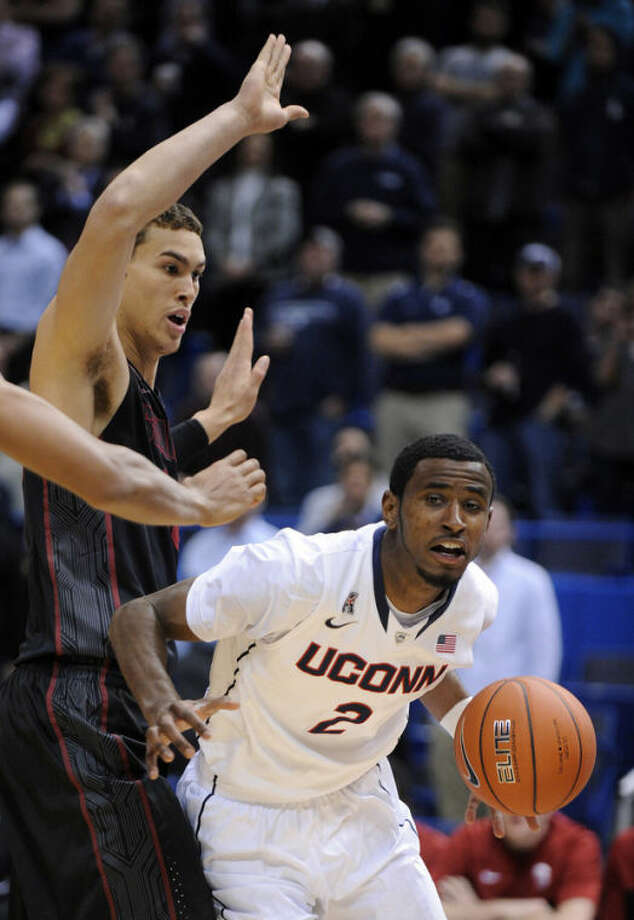 Connecticut's DeAndre Daniels (2) drives past Stanford's Dwight Powell (33) during the first half of an NCAA college basketball game in Hartford, Conn., Wednesday, Dec. 18, 2013. (AP Photo/Fred Beckham)