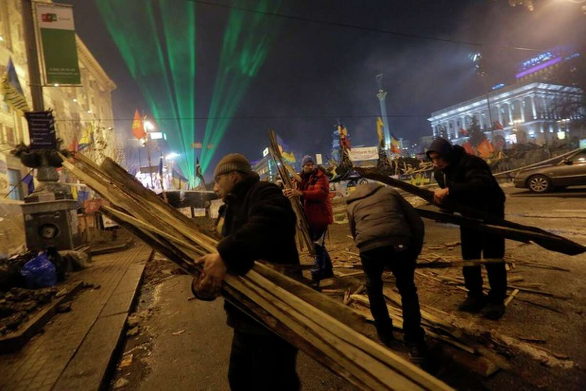Pro-European Union activists unload firewood during a rally in Independence Square in Kiev, Ukraine, Wednesday, Dec. 18, 2013. Putin and Yanukovych both pledged Tuesday, Dec. 17, 2013 to boost economic and trade ties to expand the