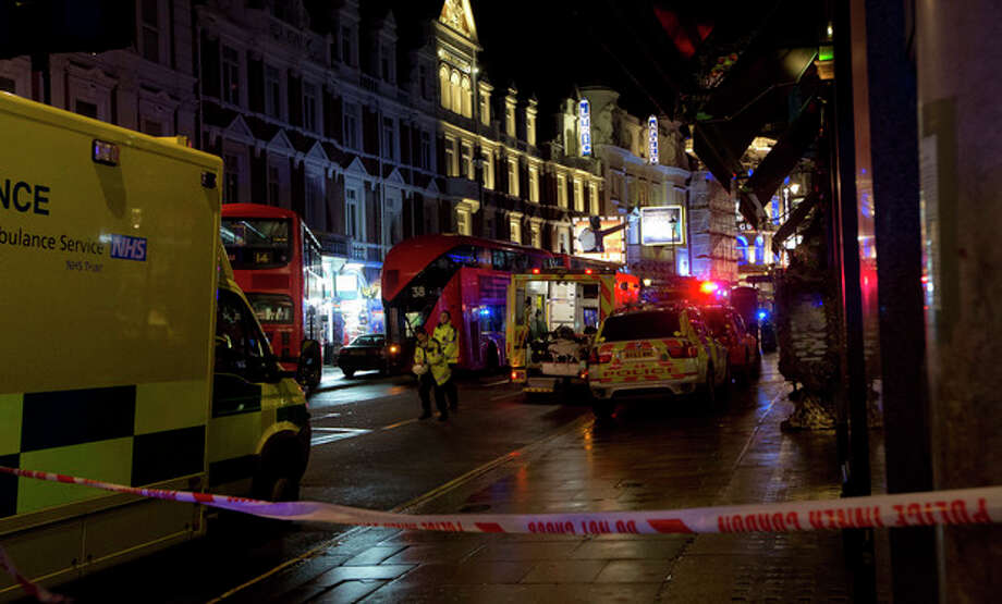 Emergency service vehicles gathered among London buses following an incident during a performance at the Apollo Theatre, far right, in London's Shaftesbury Avenue, Thursday evening, Dec. 19, 2013. It wasn't immediately clear if the roof, ceiling or balcony had collapsed. The London Fire Brigade said the theatre was almost full, with around 700 people watching the show. A spokesman said it was thought between 20 and 40 people were injured. (AP Photo by Joel Ryan, Invision) / INVISION