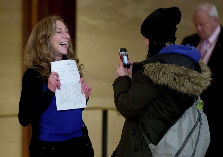 Valerie Scott holds up a copy of the ruling issued by the Supreme Court of Canada striking down the country's prostitution laws at the Supreme Court of Canada in Ottawa Friday morning, Dec. 20, 2013. The former prostitute is one of the three principles in the case. The ruling is a victory for sex workers seeking safer working conditions because it found that the laws violated the guarantee to life, liberty and security of the person. But the decision also gives Parliament a one-year reprieve to respond with new legislation. (AP Photo/The Canadian Press, Adrian Wyld) / The Canadian Press