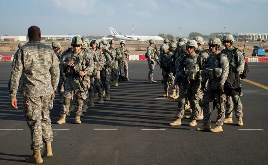 In this photo taken Wednesday, Dec. 18, 2013 and released by the U.S. Air Force, soldiers of the East Africa Response Force (EARF), a Djibouti-based joint team assigned to Combined Joint Task Force-Horn of Africa, prepare to load onto a U.S. Air Force C-130 Hercules at Camp Lemonnier, Djibouti, to support with an ordered departure of personnel from Juba, South Sudan. Gunfire hit three U.S. military CV-22 Osprey aircraft Saturday, Dec. 21, 2013 trying to evacuate American citizens in Bor, the capital of the remote region of Jonglei state in South Sudan, that on Saturday became a battle ground between South Sudan's military and renegade troops, officials said, with four U.S. service members wounded in the attack. (AP Photo/U.S. Air Force, Tech. Sgt. Micah Theurich) / U.S. Air Force